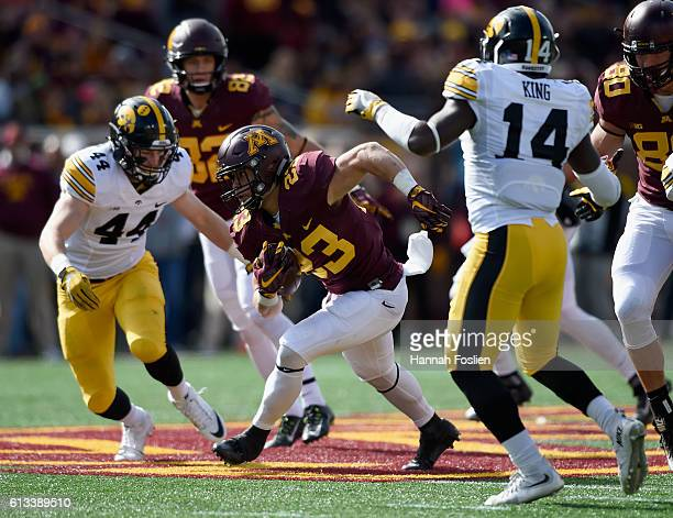 Shannon Brooks of Minnesota carries the ball against Ben Niemann and Desmond King of Iowa during the third quarter of the game on October 8 2016 at...