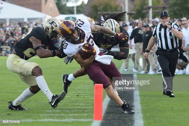 Shannon Brooks of the Minnesota Golden Gophers is pushed out of bounds by TJ McCollum and Tim Cason of the Purdue Boilermakers during the first half...
