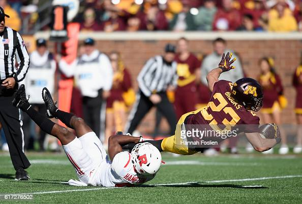 Shannon Brooks of the Minnesota Golden Gophers is tackled by Saquan Hampton of the Rutgers Scarlet Knights during the first quarter of the game on...