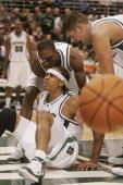 Shannon Brown of the Michigan State Spartans is helped up by teammates Maurice Joseph and Paul Davis after hitting a difficult jumper against the...