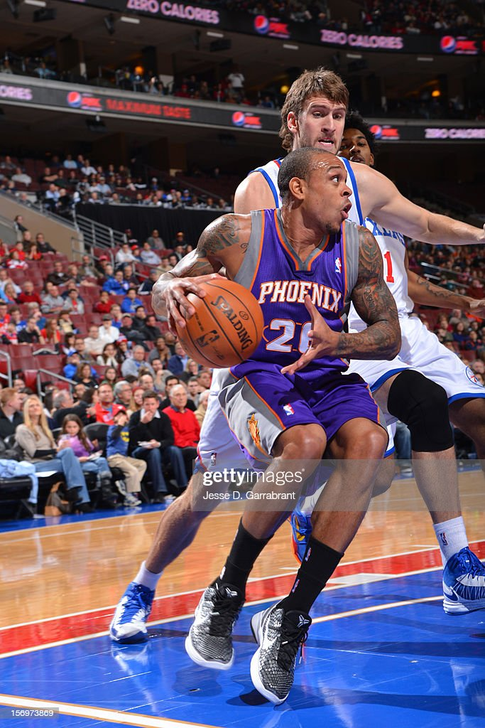 Shannon Brown #26 of the Phoenix Suns drives baseline against Spencer Hawes #00 of the Philadelphia 76ers at the Wells Fargo Center on November 25, 2012 in Philadelphia, Pennsylvania.
