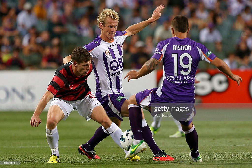 Shannon Cole of the Wanderers contest for the ball against Bas Van Den Brink and Joshua Risdon of the Glory during the round 13 A-League match between the Perth Glory and the Western Sydney Wanderers at Patersons Stadium on December 27, 2012 in Perth, Australia.