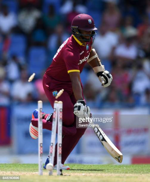 Shannon Gabriel of the West Indies is ran out by Jos Buttler of England during the 2nd One Day International match between the West Indies and...