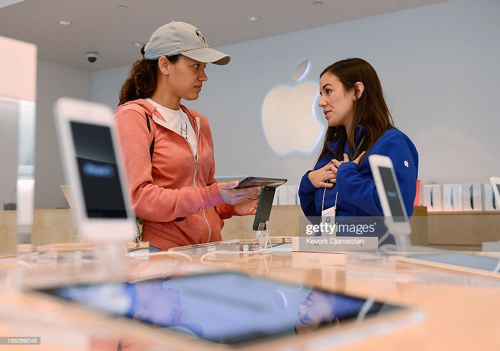 Shannon Harman (L) holds her new iPad mini as she talks to an Apple store employee on November 2, 2012 in Los Angeles, California. It was reported that lines at Apple stores nationwide were short as the new iPad mini and 4th generation iPad went on sale today.
