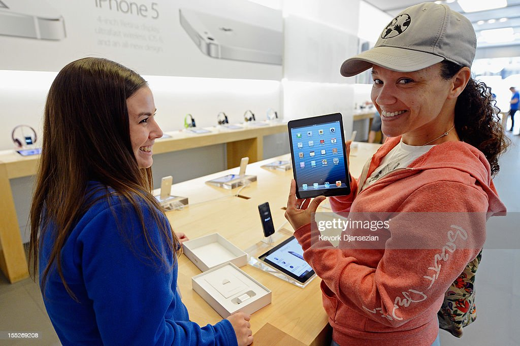 Shannon Harman (R) holds up her new iPad mini as an Apple store employee looks on after helping her on November 2, 2012 in Los Angeles, California. It was reported that lines at Apple stores nationwide were short as the new iPad mini and 4th generation iPad went on sale today.