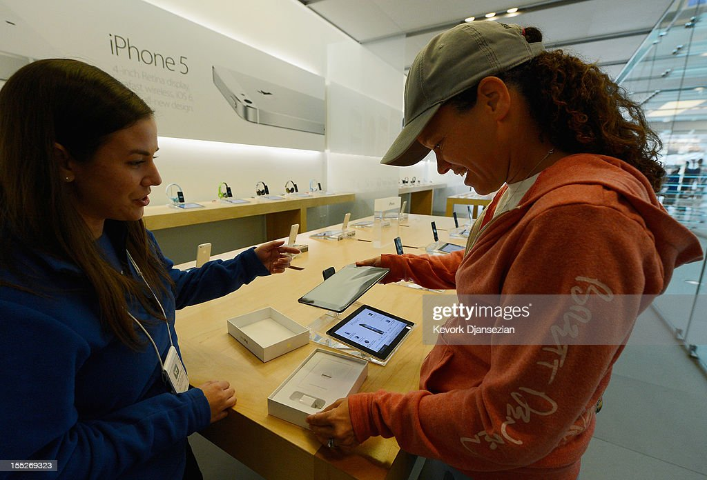 Shannon Harman (R) opens the box of her new iPad mini as an Apple store employee helps her on November 2, 2012 in Los Angeles, California. It was reported that lines at Apple stores nationwide were short as the new iPad mini and 4th generation iPad went on sale today.