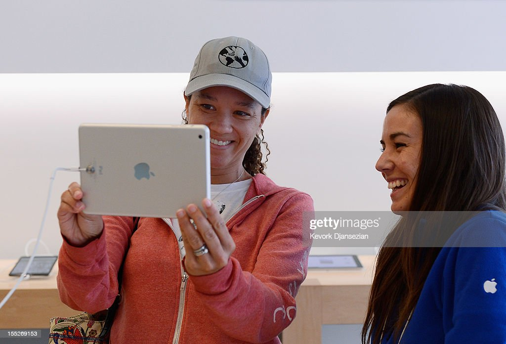 Shannon Harman (L) tests out the new iPad mini before purchasing one as an Apple employee watches on November 2, 2012 in Los Angeles, California. It was reported that lines at Apple stores nationwide were short as the new iPad mini and 4th generation iPad went on sale today.