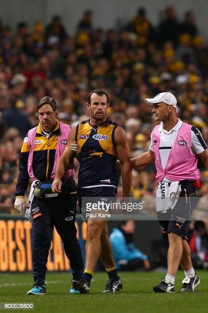 Shannon Hurn of the Eagles is assisted from the field after a heavy bump by Jack Viney of the Demons during the round 14 AFL match between the West...
