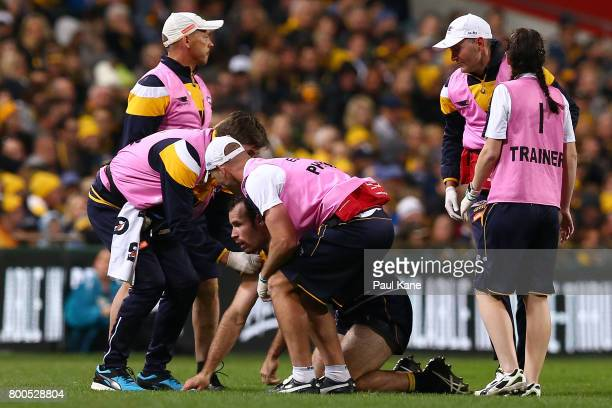 Shannon Hurn of the Eagles is attended to by trainers after a heavy bump by Jack Viney of the Demons during the round 14 AFL match between the West...
