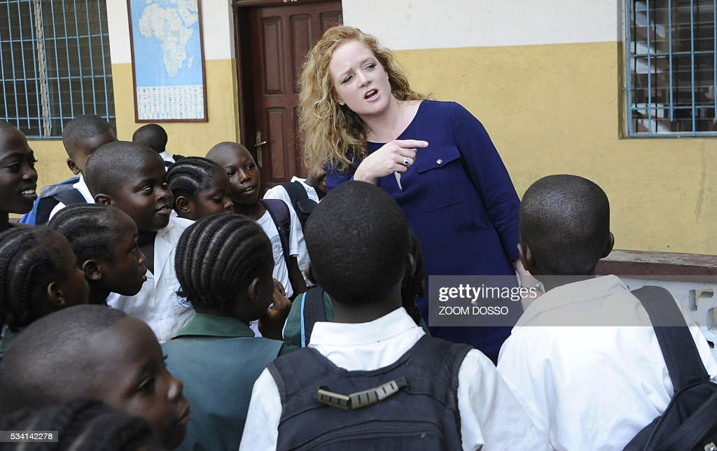 Shannon May from Bridge International Academies chain (C) chats with pupils in Monrovia on May 25, 2016. For the new school year, the Liberian government plans to roll out a public-private partnership involving 120 primary schools, costing an initial $65 million -- the equivalent of more than three quarters of the entire education budget. / AFP / ZOOM