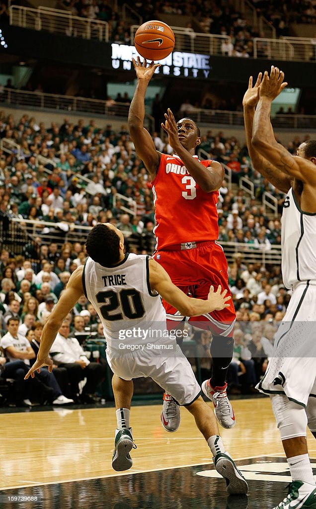 Shannon Scott #3 of the Ohio State Buckeyes gets puts up a second-half shot on a called charge against Travis Trice #20 of the Michigan State Spartans at the Jack Breslin Center on January 19, 2013 in East Lansing, Michigan. Michigan State won the game 59-56.