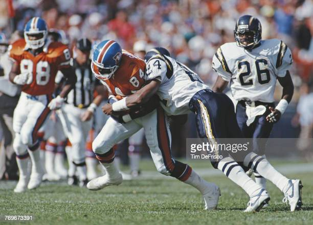 Shannon Sharpe Tight End for the Denver Broncos is tackled by Stanley Richard Defensive Back for the San Diego Chargers during the American Football...