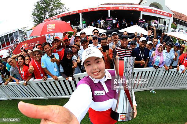 Shanshan Feng of China imitates a selfie as she poses with the Sime Darby LPGA trophy in front of cheering fans after she won it 17 under par 267...