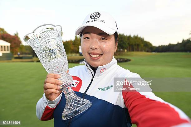 Shanshan Feng of China imitates a selfie as she poses with the trophy after winning the TOTO Japan Classics 2016 at the Taiheiyo Club Minori Course...