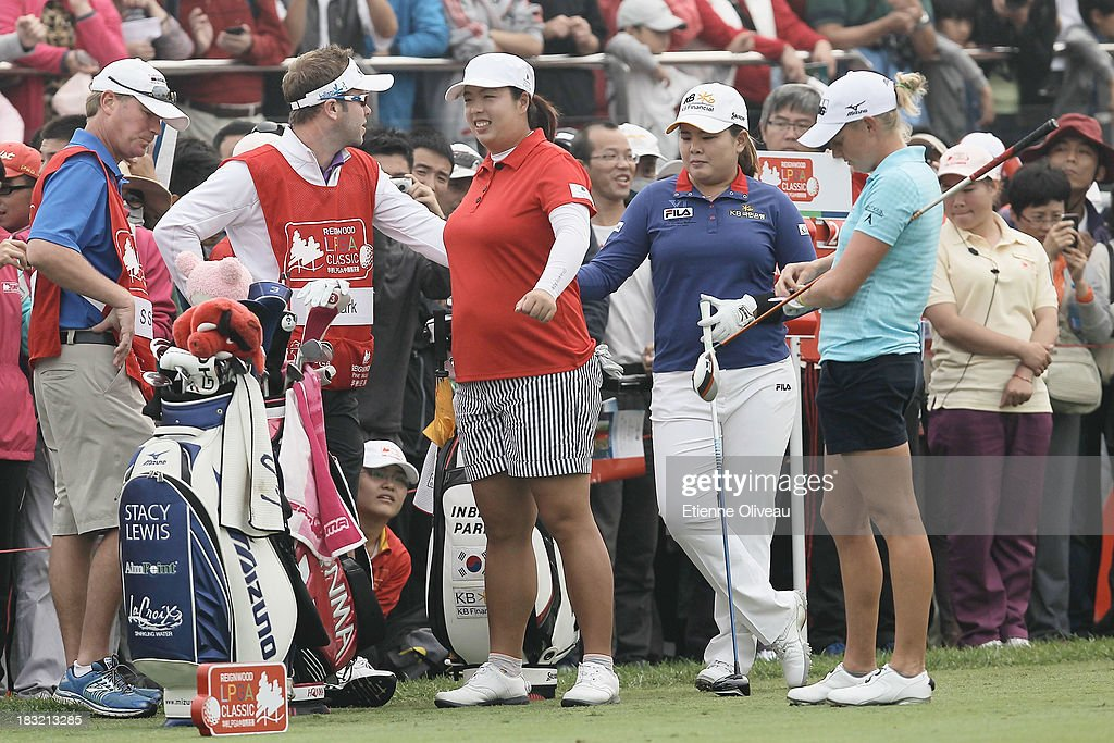 Shanshan Feng of China (left) Inbee Park of South Korea (center) and Stacy Lewis of United States (right) wait on the range with their caddies during the final round of the Reignwood LPGA Classic at Pine Valley Golf Club on October 6, 2013 in Beijing, China.