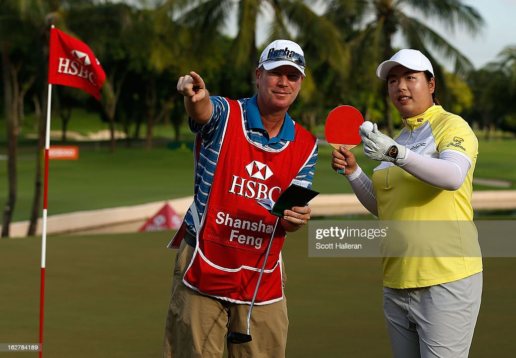 Shanshan Feng of China jokingly aims a table tennis bat with her caddie Mercer Leftwich during the pro-am prior to the start of the HSBC Women's Champions at the Sentosa Golf Club on February 27, 2013 in Singapore, Singapore.