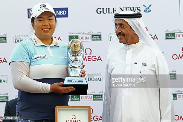 Shanshan Feng of China poses with her trophy next to Sheikh Hasher bin Maktoum alMaktoum Director General of Dubai Department of Information after...