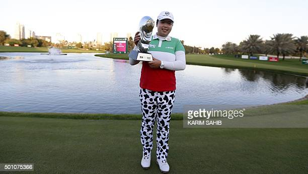 Shanshan Feng of China poses with the trophy after winning the Dubai Ladies Masters golf tournament on December 12 2015 in the Gulf emirate AFP PHOTO...
