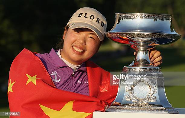 Shanshan Feng of China poses with the trophy on the 18th green after her twostroke victory at the Wegmans LPGA Championship at Locust Hill Country...