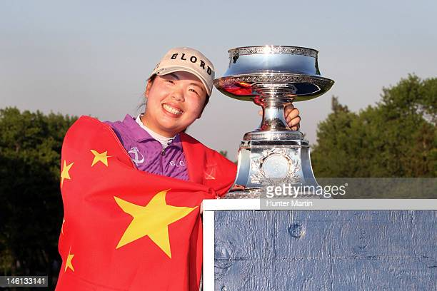 Shanshan Feng of China wraps herself in the flag of China and poses with the championship trophy after winning the Wegmans LPGA Championship at...