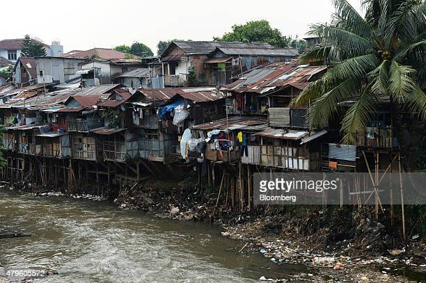 Shanty houses stand perched on stilts along a river in Jakarta Indonesia on Tuesday June 23 2015 Having watched his economic reform momentum falter...