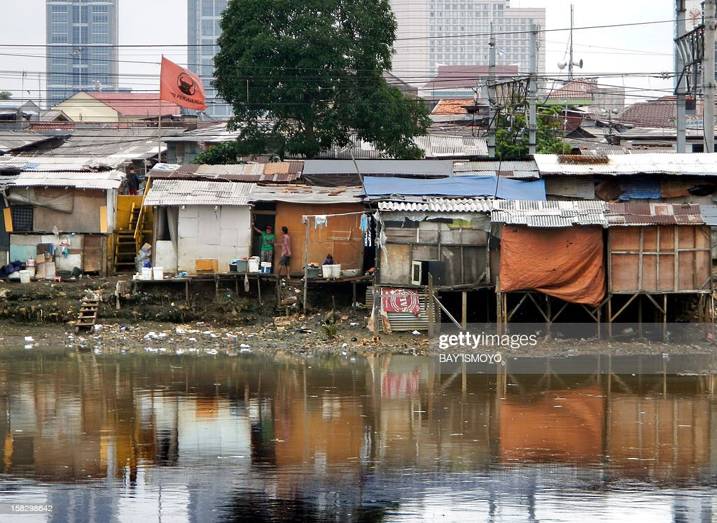 A shanty village along the banks of a river sits in front of the skyline of Indonesia's capital Jakarta on December 13, 2012. Some half of Indonesia's 240 million residents live on less than two US per day.