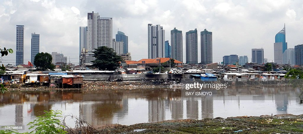 A shanty village along the banks of a river sits in front of the skyline of Indonesia's capital Jakarta on December 13, 2012. Some half of Indonesia's 240 million residents live on less than two US per day. AFP PHOTO / BAY ISMOYO