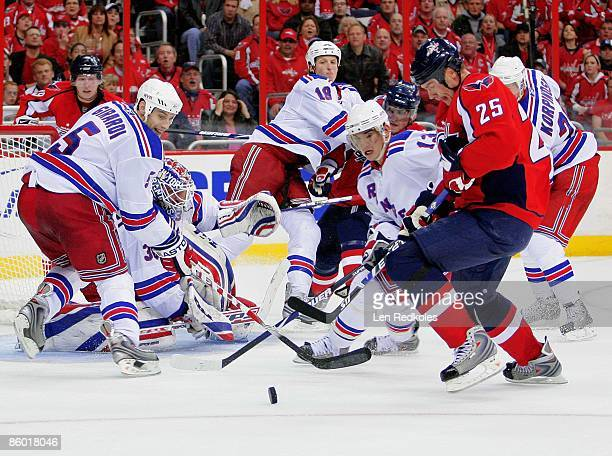 Shaone Morrisonn of the Washington Capitals attempts a backhanded shot on goal against Dan Girardi Henrik Lundqvist Marc Staal and Nikolai Zherdev of...