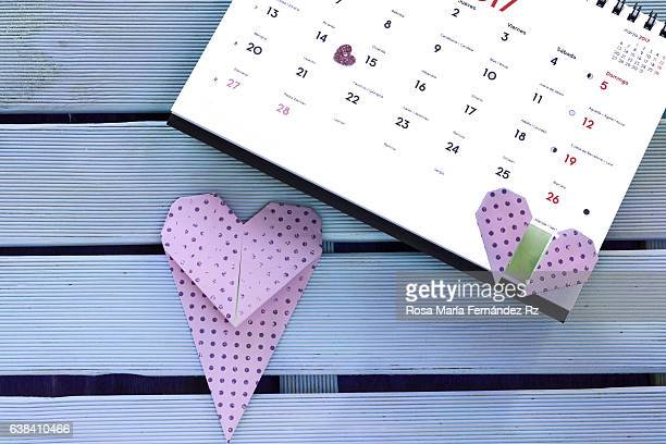 Shape heart mark on valentine's day, and origami heart bookmark on blue wooden background