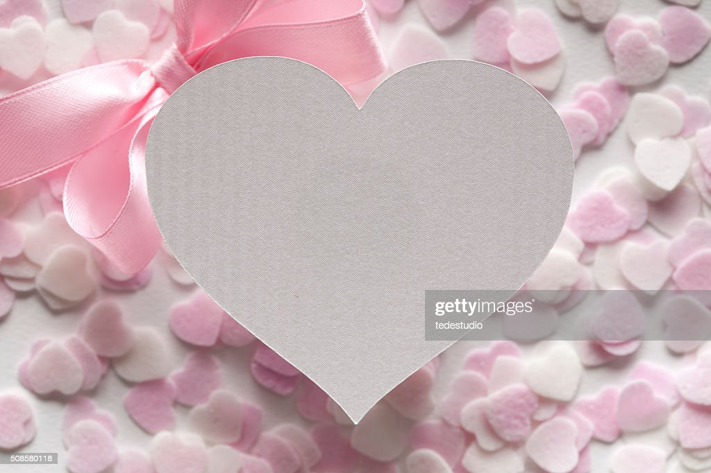 Shape of heart, pink bow and many hearts in background : Stock Photo