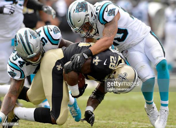 Shaq GreenThompson and Kurt Coleman of the Carolina Panthers tackle Adrian Peterson of the New Orleans Saints during their game at Bank of America...