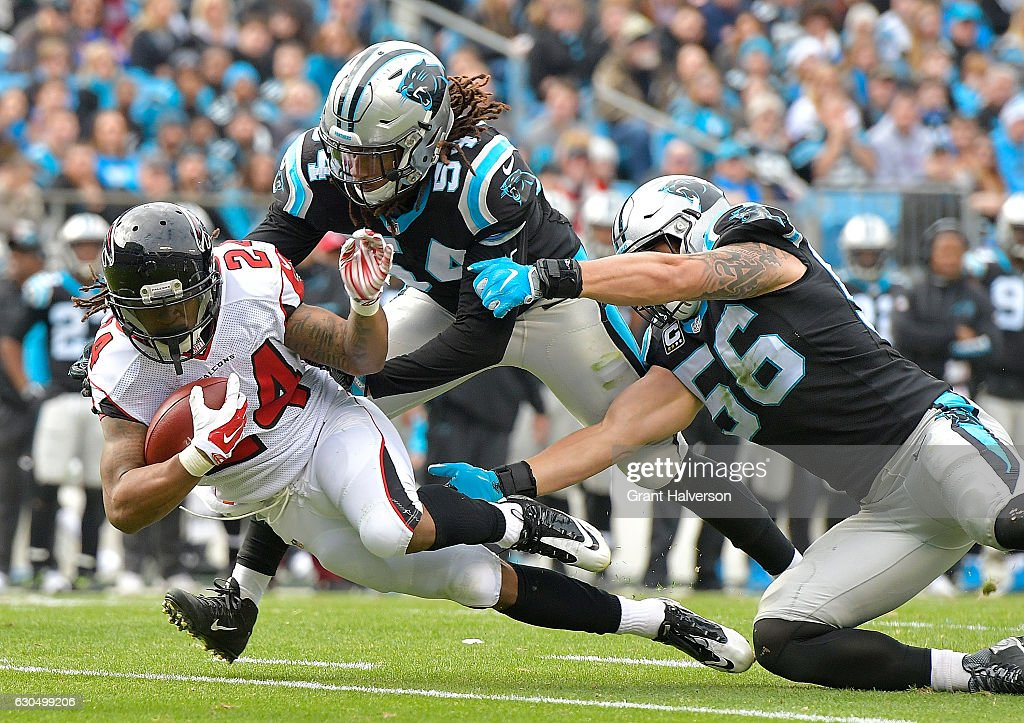 Shaq Thompson #54 and A.J. Klein #56 of the Carolina Panthers tackle Devonta Freeman #24 of the Atlanta Falcons during the game at Bank of America Stadium on December 24, 2016 in Charlotte, North Carolina.