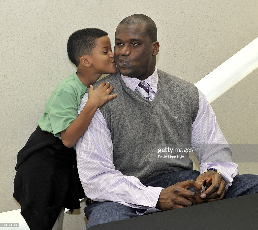 Shaqir O'Neal gives his father Shaquille O'Neal #23 of the Cleveland Cavaliers a kiss on the cheek at a book signing for Shaquille's mother Lucille O'Neal's new book 'Walk Like You Have Somewhere to Go: From Mental Welfare to Mental Wealth' prior to the game against the Milwaukee Bucks on March 31, 2010 at The Quicken Loans Arena in Cleveland, Ohio.