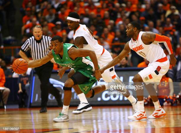 Shaquille Johnson of the Marshall Thundering Herd takes the ball down the court while being followed by Scoop Jardine and CJ Fair of the Syracuse...