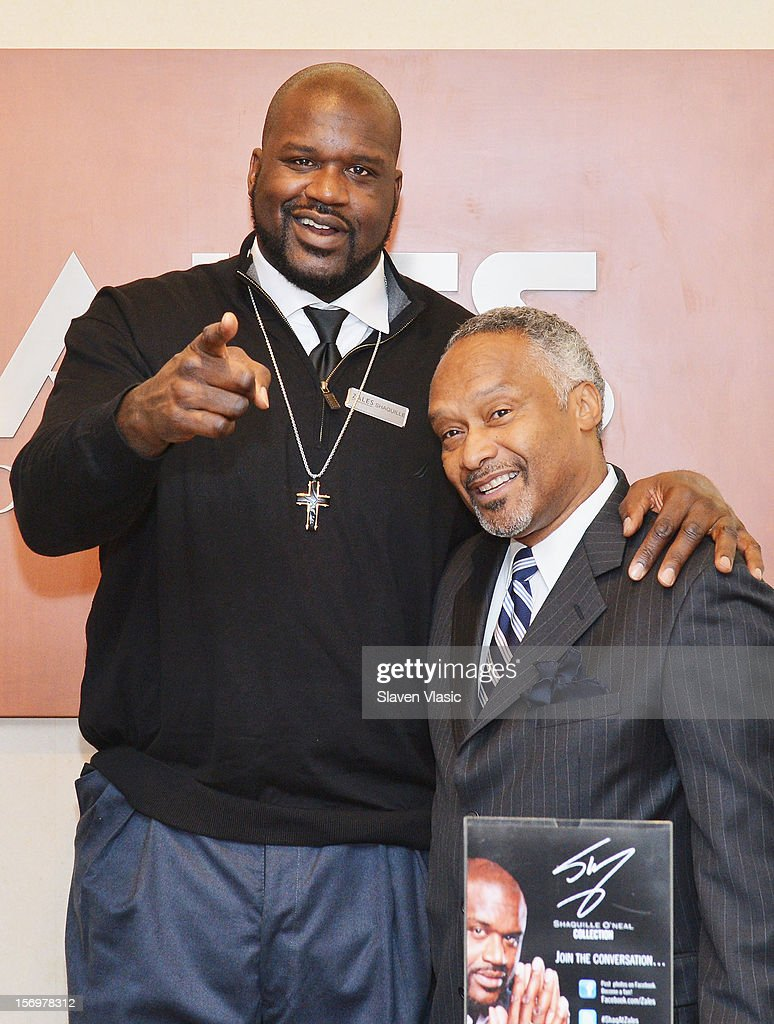 Shaquille O'Neal (L) celebrates launch of his new men's jewelry line with Zales, by helping customers from behind the counter, on November 26, 2012 in New York City.