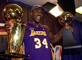 Shaquille O'Neal holds the MVP trophy and the Larry O'Brian Championship trophy after the Los Angeles Lakers won game five of the NBA Finals against...
