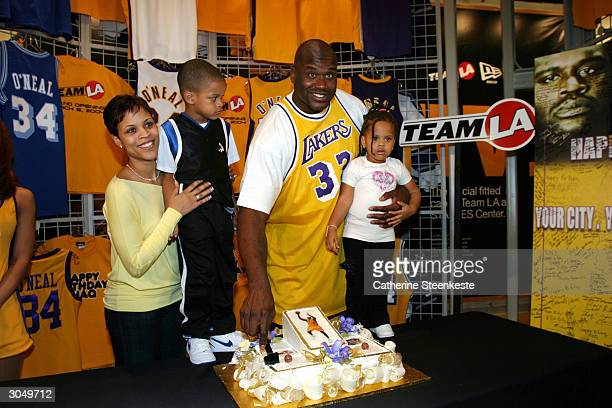 Shaquille O'Neal of the Los Angeles Lakers cut his cake with his wife Shaunie and his kids Shareef and Amirah at the opening of Team LA Store at...