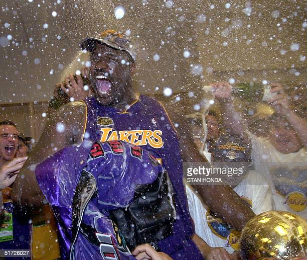Shaquille O'Neal of the Los Angeles Lakers holds the Larry O'Brian Championship trophy as he is sprayed with champagne after winning game five of the...