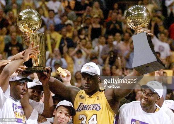 Shaquille O'Neal of the Los Angeles Lakers holds the MVP trophy and the Larry O'Brien Trophy for winning the NBA Championship 19 June after game six...