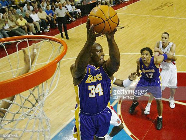 Shaquille O'Neal of the Los Angeles Lakers pulls down a rebound as Laker Rick Fox guards Tayshuan Prince of the Detroit Pistons during the first half...