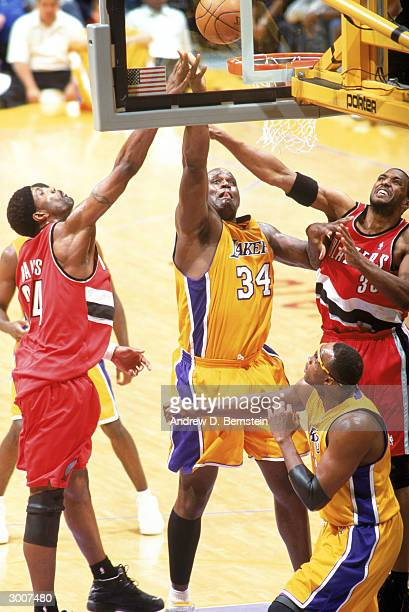 Shaquille O'Neal of the Los Angeles Lakers shoots a layup between Dale Davis and Shareef AbdurRahim of the Portland Trail Blazers during the game at...