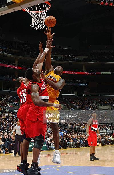 Shaquille O'Neal of the Los Angeles Lakers shoots over Dale Davis and Shareef AbdurRahim of the Portland Trail Blazers during the game on February 17...