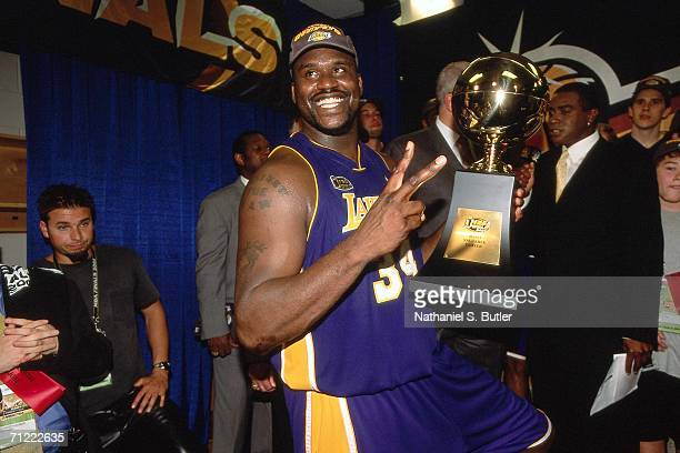 Shaquille O'Neal of the Los Angeles Lakers shows off his NBA Finals MVP trophy after winning the 2001 NBA Championship by defeating the Philadelphia...