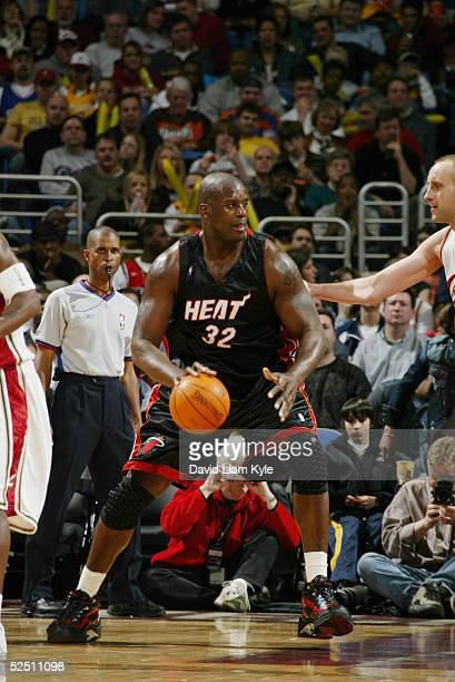 Shaquille O'Neal of the Miami Heat is defended by Zydrunas Ilgauskas of the Cleveland Cavaliers during the game at Gund Arena on March 6 2005 in...