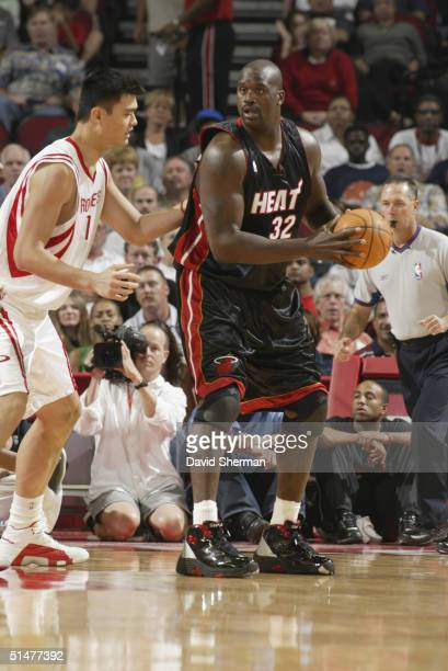 Shaquille O'Neal of the Miami Heat moves the ball against Yao Ming of the Houston Rockets during the preseason game at Toyota Center on October 10...