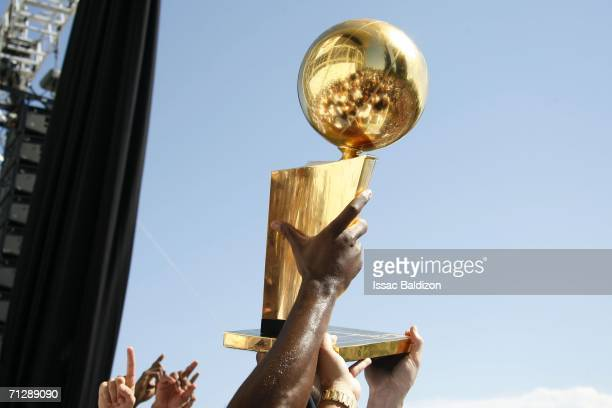 Shaquille O'Neal of the Miami Heat shows off the Larry O'Brien trophy during the victory parade at American Airlines Arena on June 23 2006 in Miami...