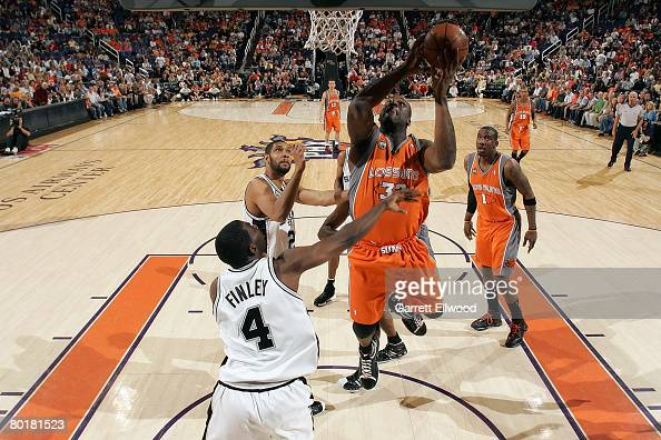 Shaquille O'Neal of the Phoenix Suns goes to the basket against Tim Duncan and Michael Finley of the San Antonio Spurs at the US Airways Center March...