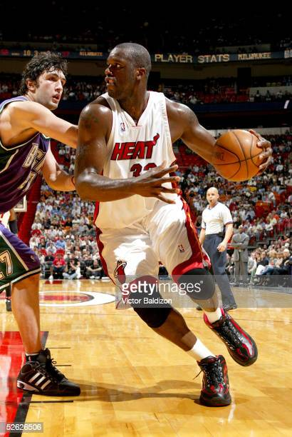 Shaquille O'Neal#34 of the Miami Heat drives around Zaza Pachulia#27 of the Milwaukee Bucks during NBA action on March 14 2005 at American Airlines...