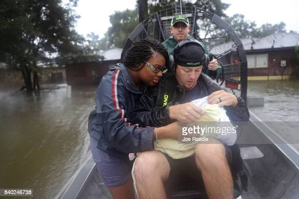 Shardea Harrison looks on at her 3 week old baby Sarai Harrison being held by Dean Mize as he and Jason Legnon used his airboat to rescue them from...