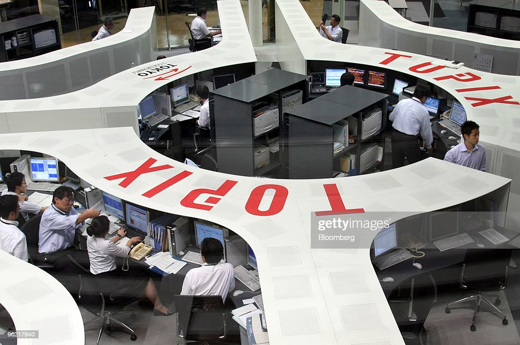 Share brokers sit in front of monitor displays at the Tokyo Stock Exchange in Tokyo Japan on Tuesday Sept 16 2008 Asian stocks plunged the most in...